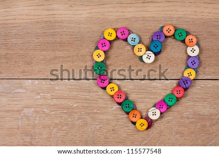 Valentine Heart of color buttons on wooden background