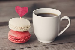 valentine macaroons with coffee on wooden table. Toned image