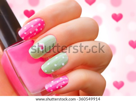 Valentine Nail art manicure. Valentine\'s Day Holiday style bright Manicure with painted hearts and polka dots. Bottle of Nail Polish. Beauty salon. Hand. Trendy Stylish Colorful Nails, Nailpolish