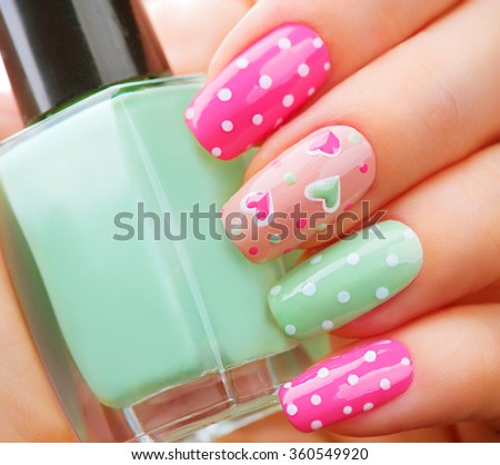 Valentine Nail art manicure. Valentines Day Holiday style bright Manicure with painted hearts and polka dots. Bottle of Nail Polish. Beauty salon. Hand. Trendy Stylish Colorful Nails, Nailpolish