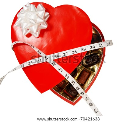 Valentine's candy heart wrapped in a tape measure - concept of the gift of an expanding waistline