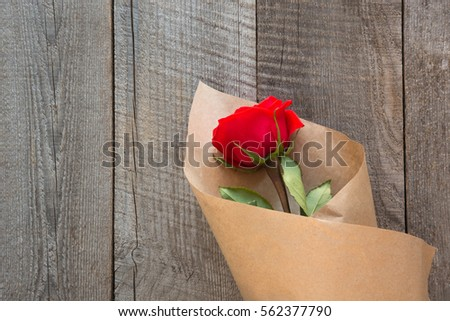 Valentine's card. Red roses wrapped in paper on wooden table background. Top view.