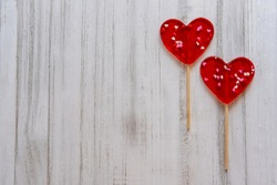 Valentine's card. Two Lollipops as heart on wooden background. Banner of sweet heart shaped candies on white background. Love concept.