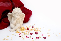 Valentine's Day. Angel on a white background with a red cloth, gold powder with hearts.