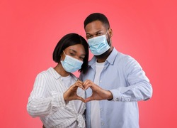 Valentine's Day at times of coronavirus. Romantic African American couple making heart with hands, wearing protective masks on pink background. Black sweethearts demonstrating love gesture
