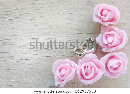 valentine's day background, border pink roses, two silver heart on wooden table #562959550