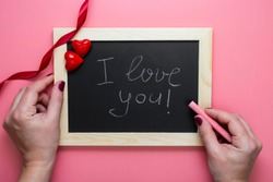 Valentine's day background. Female hands writting I love you message on chalkboard frame, hearts and red ribbon, flat lay mock up with copy space. Greeting card.