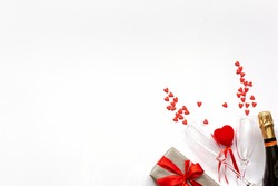 Valentine's Day background. Gift box, red hearts, two champagne glasses, bottle champagne on white background.Concept: Valentines day, wedding, birthday.Flat lay, top view, copy space.