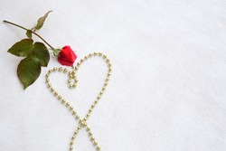 Valentine's Day background: red rose and a heart from golden like perls. Free space for a text.