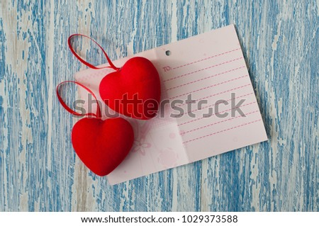 Valentine's day, background with space for copy. Valentine card and red hearts on a wooden background