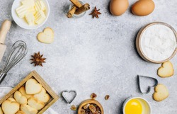 Valentine's Day baking culinary background. Ingredients for cooking on wooden kitchen table, baking recipe for pastry. Heart shape cookies. Top view. Flat lay.