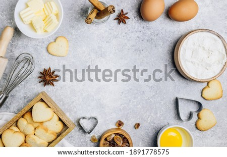 Valentine's Day baking culinary background. Ingredients for cooking on wooden kitchen table, baking recipe for pastry. Heart shape cookies. Top view. Flat lay. Stock foto ©