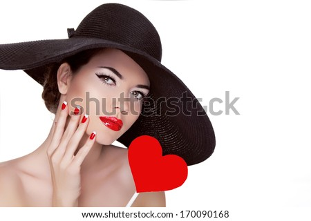 Valentine's Day. Beautiful woman with heart in her hand wearing in elegant hat. Makeup. Manicured nails. Beauty portrait of attractive girl.