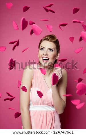Valentine's day. Beautiful young woman with hearts falling around her.