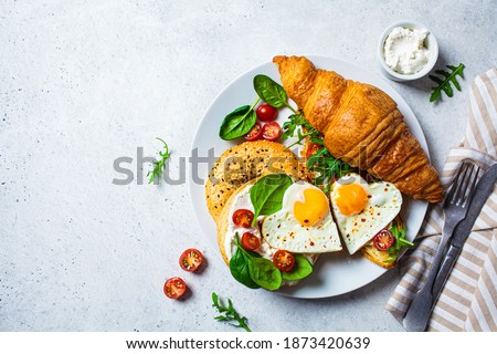 Valentine's day breakfast concept. Sandwich with croissant, bagel, cream cheese and fried eggs hearts on a white plate. Photo stock ©