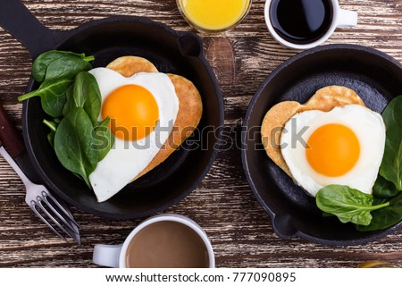 Valentine's day breakfast or brunch. Homemade  heart shape fried egg and pancake in cast iron skillet  with spinach, orange juice and cup of coffee. Table viewed from above #777090895