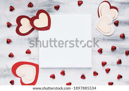 Valentine's Day card blank canvas with a variety of hearts over a wooden background. Copy space for text. Image shot from top view.