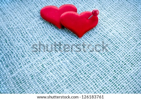 Valentine\'s day card,  red heart symbol with needle on fabric sack texture background