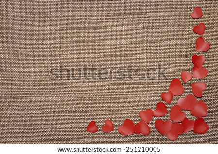 Valentine\'s day card with red hearts on fabric sack texture background