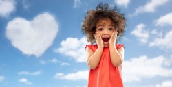 valentine's day, childhood and emotions concept - surprised or scared little african american girl screaming over blue sky and heart shaped cloud background