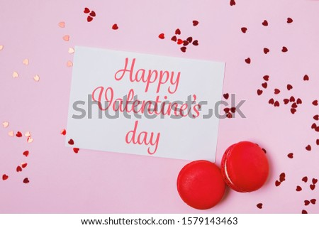 Valentine's day composition with greeting card with text, two macarons and heart shaped confetti on pink background, top view. Happy Valentine's day.