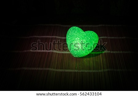 Valentine's Day composition with sweet burning multicolored heart on dark background, selective focus, or love greeting card of heart red green pink yellow #562433104