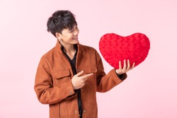 Valentine's day concept, Asian a man handsome young holding a red heart shaped pillow in love isolated on pink blank copy space studio background.
