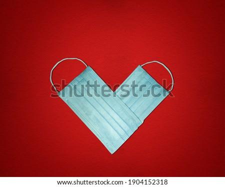 Valentine's Day concept background. Valentine's day concept background for covid-19 with love shaped mask. Creative Valentine day and coronavirus concept on red background.