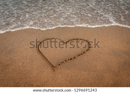 Valentine's day concept. Heart drawn on the shore Couple celebrating valentine's day near the sea at the beach. Icon of love Love is beautiful and forever. Lovely holiday landscape exotic postcard #1296691243