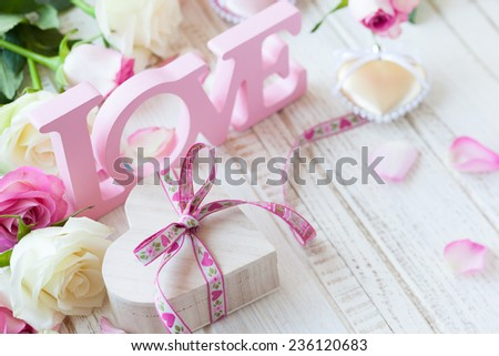 """Stock Photo Valentine's day concept with gift box, letters """"love"""" and flowers on old vintage wooden background"""