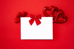 Valentine's day congratulation. Red rose and greeting card with heart sign on red background top view copy space