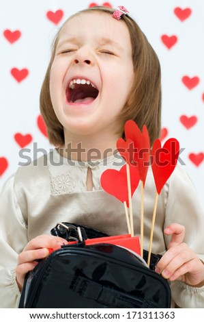 Valentine\'s Day - dreaming cute child holding red hearts