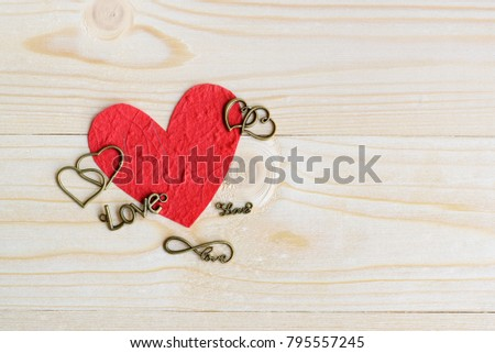 Valentine's day / endless love or special occasion concept : Top / overhead view of big red heart with brass heart on wood texture background with copy space. Depicts love passion for romantic couple.