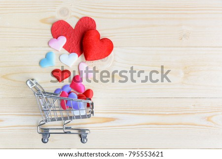 Valentine's day / endless love or special occasion concept : Top / overhead view of red, pink, white, blue hearts fall or spilled out of a shopping basket on wood texture background with copy space