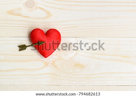 Valentine's day / endless love or special occasion concept : Top / overhead view of red velvet heart with brass arrow on wood texture background, copy space. Depicts love passion for romantic couple.