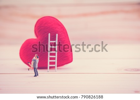 Valentine's day / eternal love or special occasion concept : Love couple miniature figurine hug / embrace each other to express affection near a red pillow heart with a white ladder on wood floor.