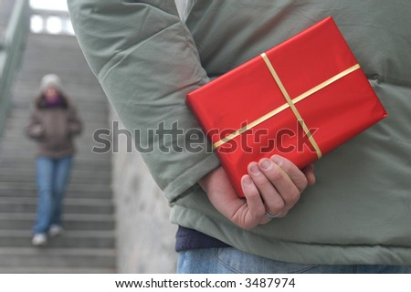 Valentine's Day Gift. Young man with a red gift box waiting for a girl - stock photo