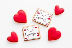 Valentine's Day. Gingerbread cookies in the shape of a red heart,  with the image of a couple in love and a love letter.White background top view,flat lay, mockup