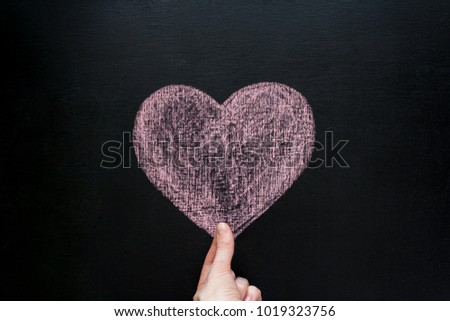 Valentine s day. Hand holds the heart, painted with chalk on on black chalkboard #1019323756
