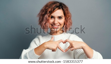 Valentine's Day. Happy young woman depicts heart with her fingers and rhythmically moves to camera at interlocutor, smiling. Symbol of love, Valentine's Day. Holiday of all lovers. Feelings, emotions
