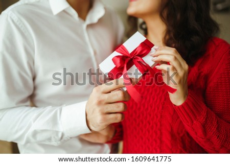 Valentine's Day, holiday and surprise concept. Man gives to his woman a gift box with red ribbon. A loving couple cuddles and celebrating Valentine's Day in the restaurant. Lovers give each other gift