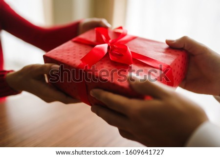 Valentine's Day, holiday and surprise concept. Man gives to his woman a red gift box. A loving couple celebrating Valentine's Day in the restaurant. Lovers give each other gifts.