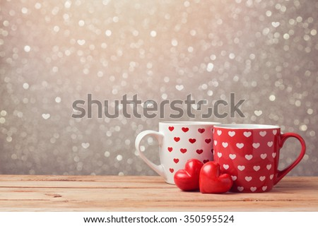 Valentine\'s day holiday celebration with hearts and cups over bokeh background