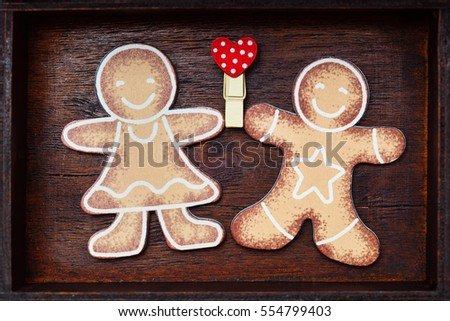 Valentine's Day. Lovers gingerbread men holding red heart (love symbol) on wooden background. #554799403