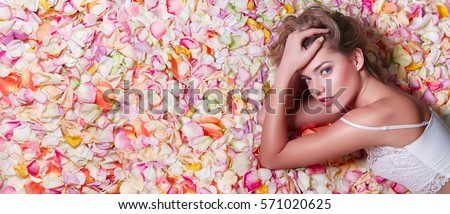 Stock Photo Valentine's Day. Loving girl. The girl in white dress lying on the floor in the petals of roses. Background of white, orange, red, pink rose petals. Pink lipstick on the lips from the beautiful girl.