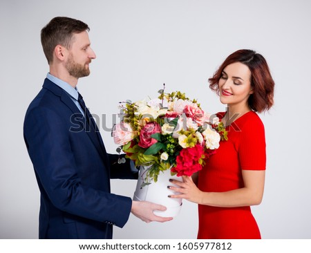 Valentine's day or birthday surprise concept - handsome man surprising his girlfriend with flowers over white background