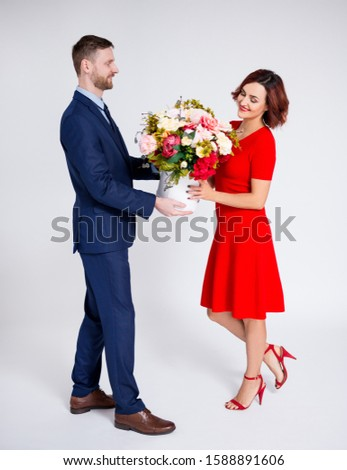 Valentine's day or birthday surprise concept - man surprising his girlfriend with flowers over white background