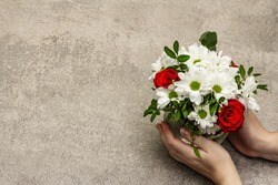 Valentine's Day or Wedding or Happy Birthday concept. Female hands are holding a bouquet of flowers. Grey stone concrete background, copy space