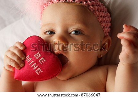 Valentine\'s day picture of baby chewing on a heart that says Be Mine on white fabric surface
