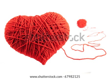 Valentine's Day. Red heart shape symbol made from wool isolated on white background